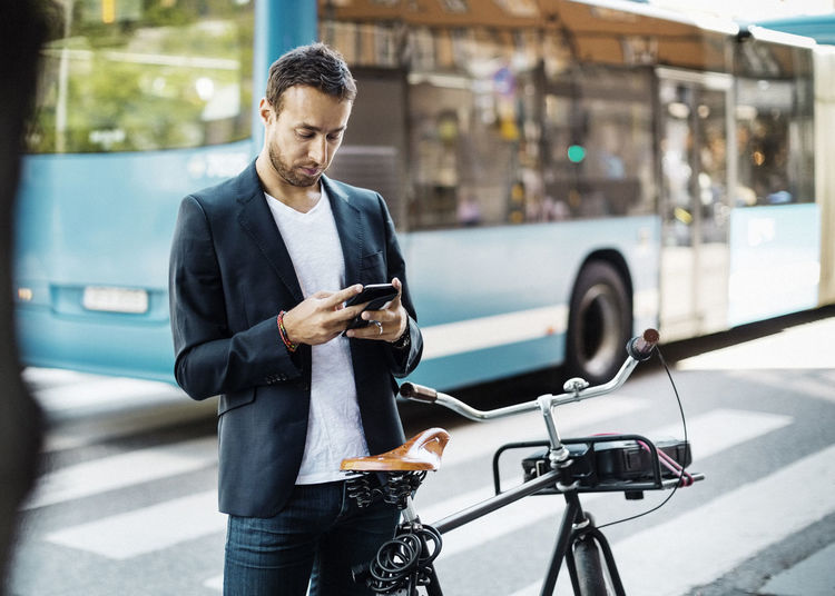 Man using mobile phone on street in city