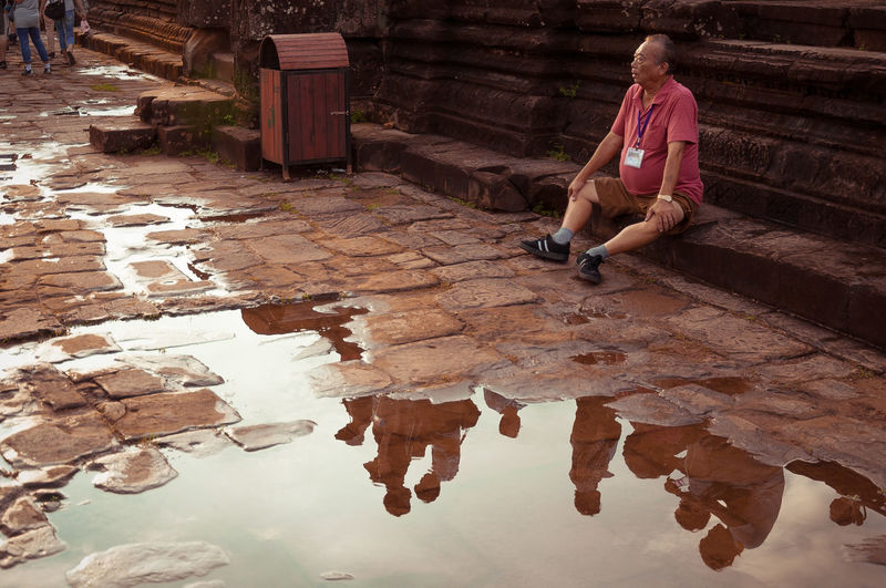 2012 APS-C Angkor Wat, Cambodia DSLR Randmotiv Tourist Attraction  Adult Built Structure Casual Clothing Leisure Activity Nklb One Person Puddle Reflections Real People Relaxation Sitting Tour Guiding