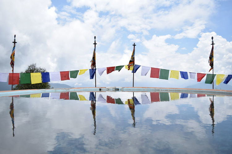 Reflection Of Colorful Flags In Water Against Cloudy Sky
