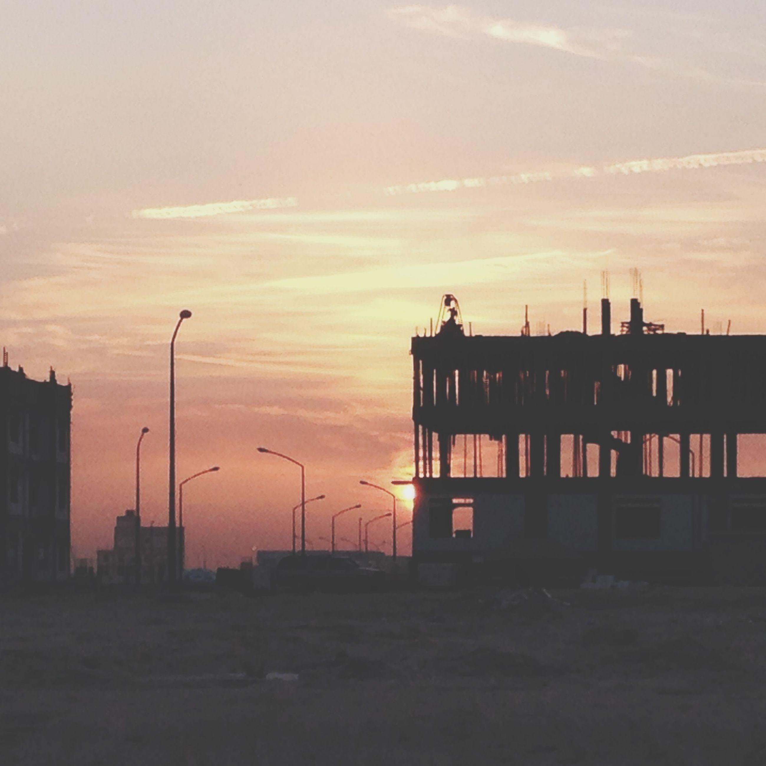 sunset, building exterior, architecture, built structure, sky, silhouette, orange color, city, cloud - sky, residential structure, building, residential building, outdoors, street light, transportation, house, dusk, cloud, nature, no people