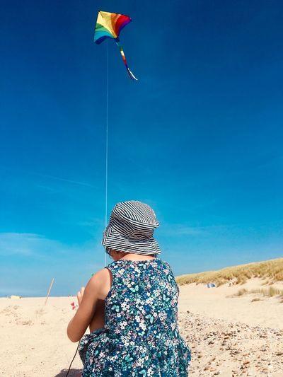 Rear view of girl wearing hat flying kite against sky