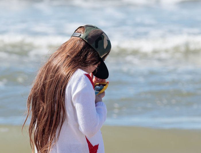Girl using smart phone while standing on sea shore at beach