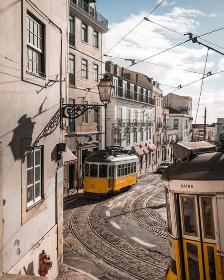 two yellow trams Building Exterior Architecture Cable Built Structure Transportation Power Line  Railroad Track Mode Of Transport City Sky Street Outdoors Day Residential Building Land Vehicle Public Transportation Electricity Pylon Cloud - Sky Electricity  Town Lisbon LisboaLumix GH5