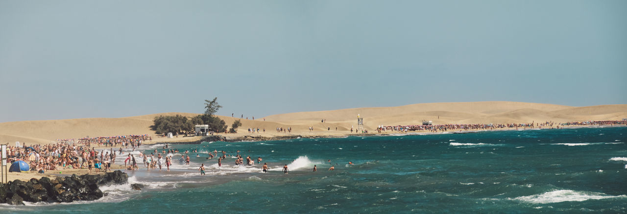 Panoramic view of people at beach against clear sky