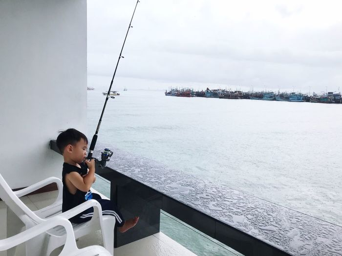Cute Boy Fishing While Sitting At Balcony