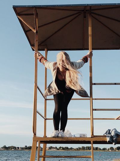 Portrait of woman standing on lifeguard hut at beach