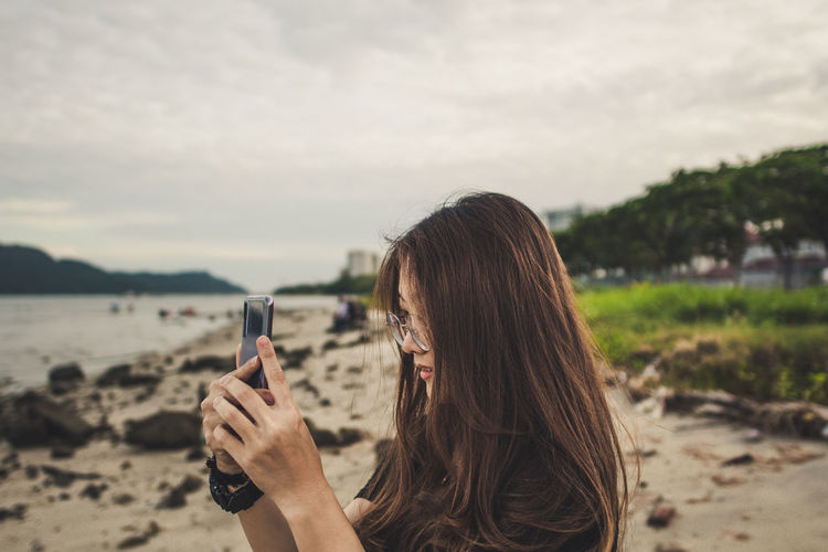 Phone photography Beach Communication Focus On Foreground Girl Hair Hairstyle Headshot Holding Land Leisure Activity Lifestyles Long Hair Mobile Phone Nature One Person Outdoors Portrait Real People Sky Technology Water Wireless Technology First Eyeem Photo