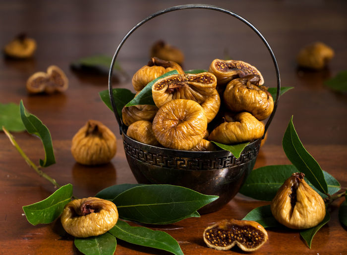 a basket of dried figs and laurel leaves as a spice Vegetarian Autumn Fruits Bowl Close-up Dried Figs Figs Flavored Focus On Foreground Food Fruit Green Color Healthy Healthy Eating Indoors  Laurel  Laurel Leaves Leaf No People Plant Part Sliced Fruits Still Life Table Tasty Wellbeing Wood - Material