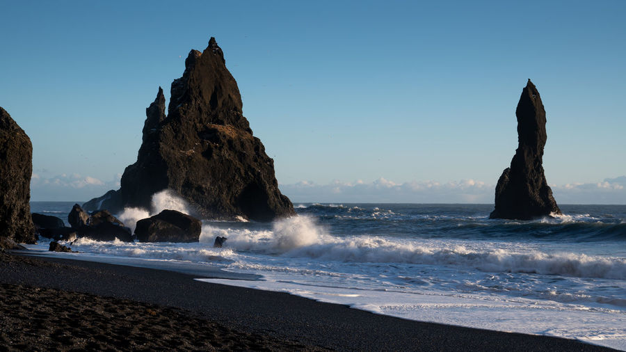Panoramic image of the rock spires of Reynisdrangur with basalt rocks, coast of Reynisfjara close to Vik, Iceland, Europe Sea Water Beach Land Sky Beauty In Nature Rock Scenics - Nature Solid Nature Rock - Object No People Rock Formation Horizon Over Water Outdoors Vík í Mýrdal Iceland Reynisdrangur Reynisfjara Travel Travel Destinations Tourism Nature Landscape Dusk Dawn Sundown Sunset Panorama Panoramic Cliff Coast Coastline Coastal Feature