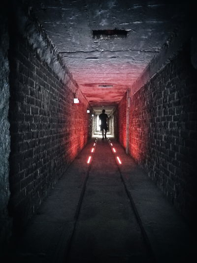 Into the light... Architecture Red Light Silhouette Men Illuminated Tunnel Built Structure Architecture Passageway vanishing point Light At The End Of The Tunnel Spooky Underground Walkway Pathway Passage Creative Space