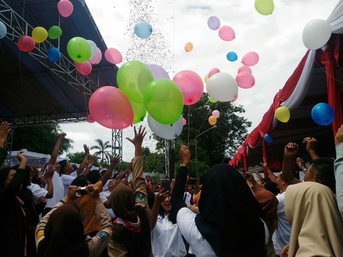 People Celebrating With Colorful Balloons At Street