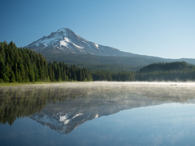 View of Mount Hood from Trillium Lake. A man and his dog float on the boat. Mount Hood Mount Hood Sunrise Peace Skies Blue Boat Dog Fog Foggy Lake Mount Hood National Forest Mountain Peaceful Sunrise Trillium Lake Camp Lost In The Landscape