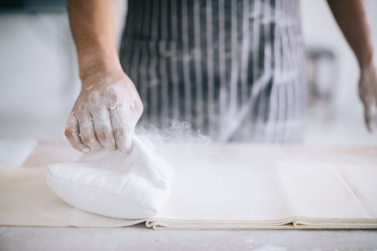 Midsection of chef using flour to make noodles
