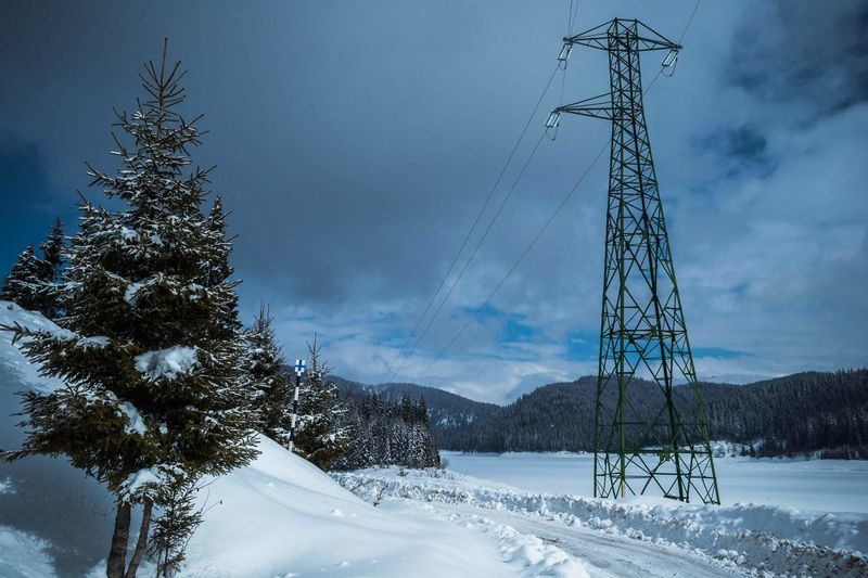 Electricity pylon on snow covered land against cloudy sky