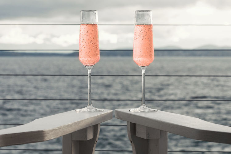 Two flutes of pink champagne on seaside deck. Adirondack Chairs Bubbles Carbonated Champagne Cruise Ship Toasting View Alcohol Balcony Celebrating Cheers Close-up Day Deck Drink Flutes Focus On Foreground Ocean Outdoors Pink Refreshment Sailing Sea Sky Water