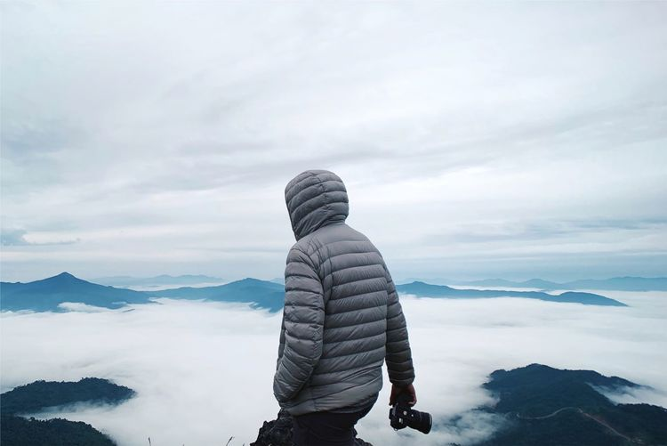Man Walking On Mountain Against Cloudscape