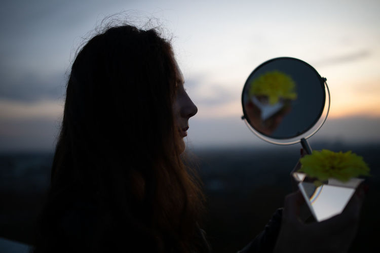 Close-up of woman holding mirror against sky during sunset