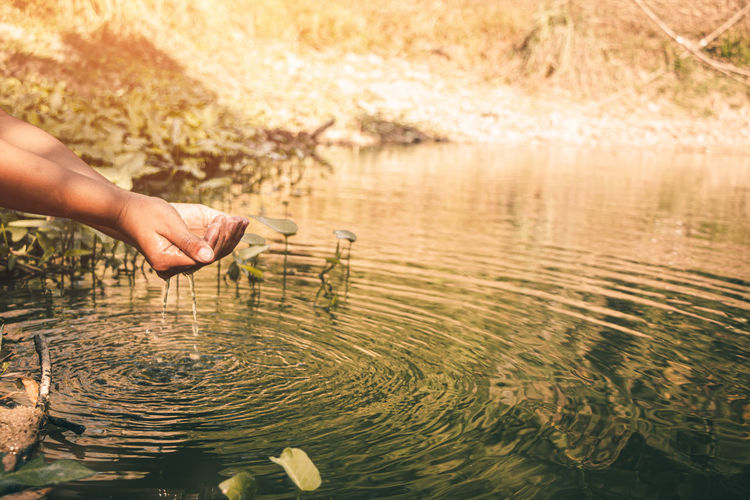 Midsection of man touching water in lake