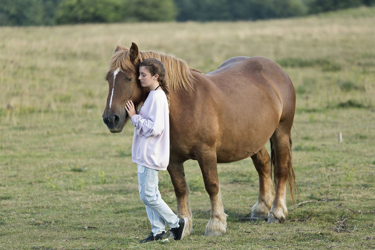 Woman with horse walking on field