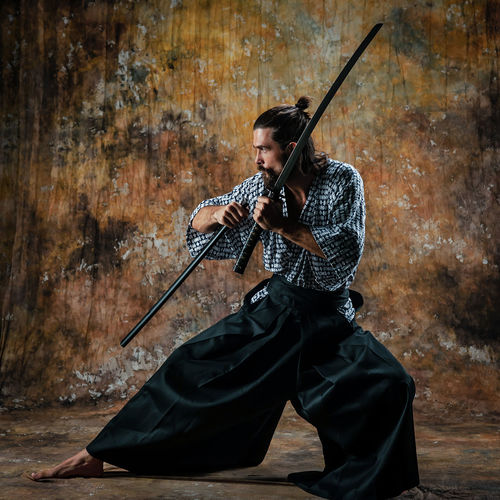 Handsome young man in traditional Japanese kimano clothes. The guy with the Japanese katana sword. He has long hair and a beard. This is a warrior. Emotions on the face. Studio photography. Portrait. Katana Sword Samurai Japan Japanese  Traditional Tradition Traditional Clothing Portrait One Person One Man Only People People Watching people and places Worrior Soldier Man Males  Male Lifestyles Lifestyle Kimono Emotion Emotions Hair Hairstyle Beard Facial Hair Ninja Real People Holding Weapon Leisure Activity Conflict Sport Gun Fighting Warrior - Person Adult Young Adult Anger Men Full Length Aggression