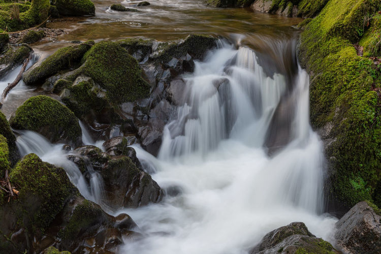 Long exposure of a waterfall flowing over rocks at watersmeet in exmoor national park