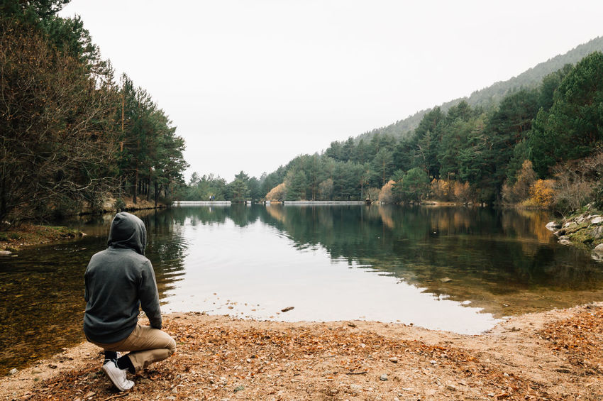 Man looking at the mountain lake Beauty In Nature Casual Clothing Day Full Length Lake Leisure Activity Lifestyle Lifestyles Mountain Mountains Nature Non-urban Scene Outdoors Rear View Reflection Remote Scenics Sky Solitude Squat Tourism Tranquil Scene Tranquility Tree Water