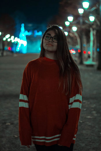 Young woman standing against illuminated wall at night