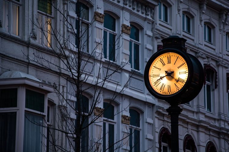 Low Angle View Of Illuminated Clock Against Building At Dusk