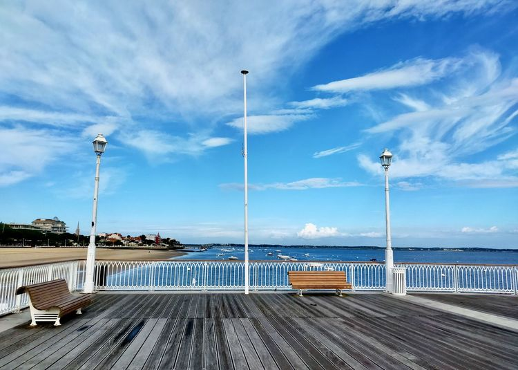 Street by pier against sky