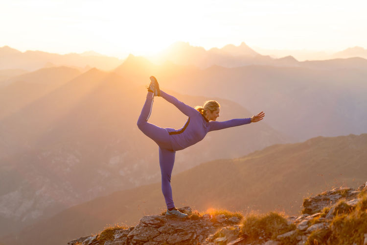 Woman practicing yoga on mountain peak during sunrise