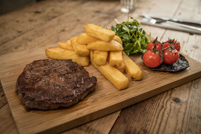 I'll have the steak Beef Burger Chunky Chips Close-up Country Pub Cutting Board Day Food Food And Drink Food On Board Freshness Hamburger Indoors  Meat No People Ready-to-eat Ribeye Steak Rustic Steak Sussex Table Unhealthy Eating Vegetable Wood - Material Wooden Table