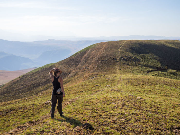 Full length of young woman hiking in drakensberg mountains at highmoor nature reserve, south africa