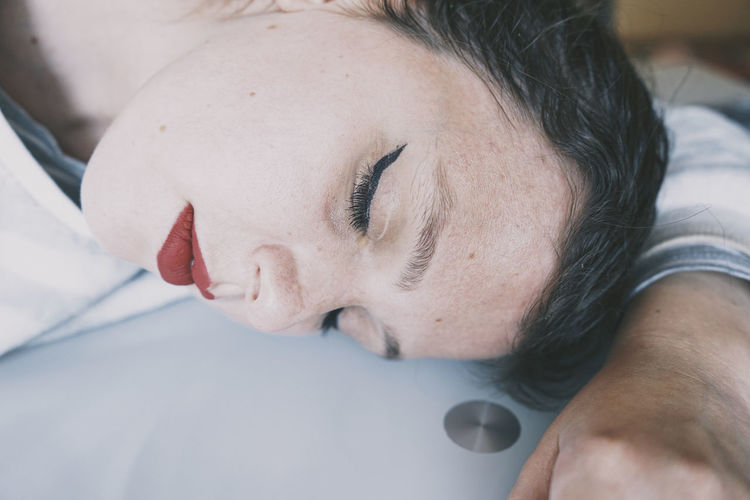 Close-up portrait of woman lying down on bed