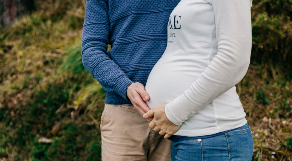 Midsection of pregnant woman standing with man on field