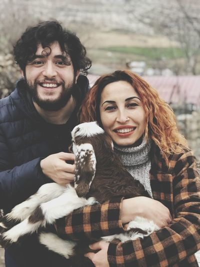 Portrait of smiling couple with kid goat