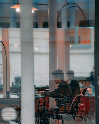 People in city street seen through glass window