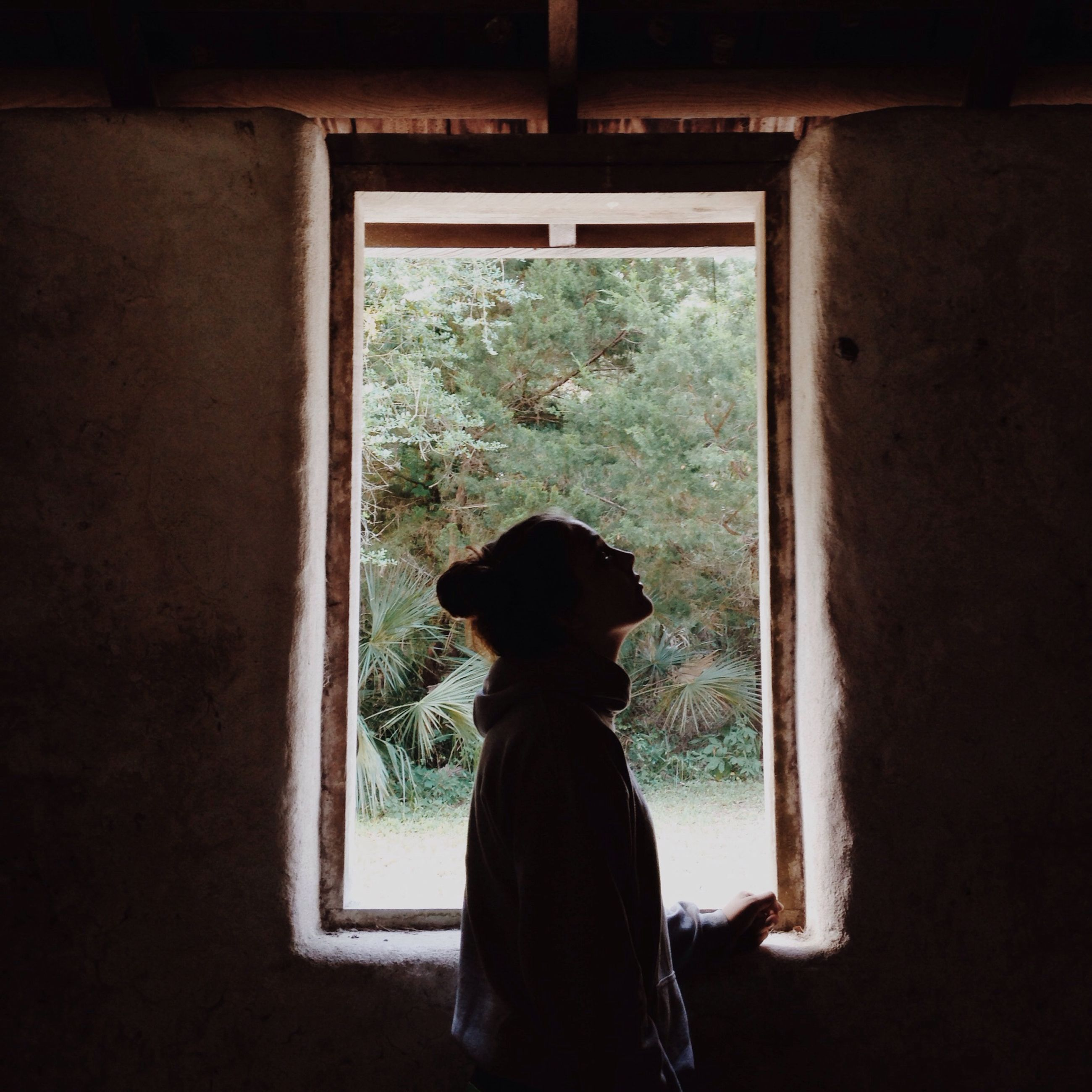 indoors, window, lifestyles, standing, silhouette, rear view, home interior, architecture, built structure, looking through window, glass - material, leisure activity, person, full length, house, wall - building feature, transparent, three quarter length