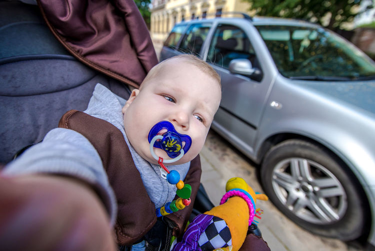 Close-up of baby boy sitting in stroller against car