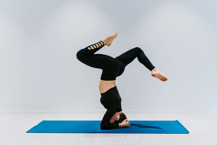 Full length of woman performing headstand against white background