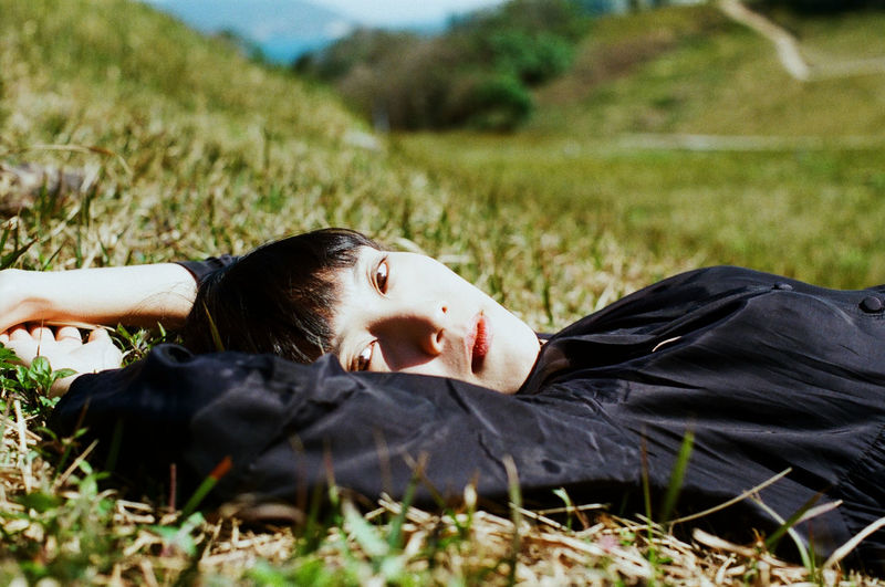 REBEL YOUNG WOMAN LYING DOWN ON FIELD
