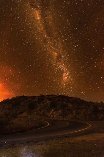 Winding road by hill with stars in sky at night