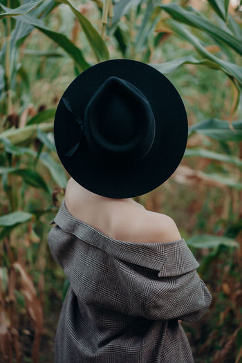 Rear view of woman wearing hat standing amidst plants