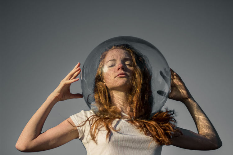 Low Angle Portrait Of Young Woman Wearing Glass Helmet In Head Against Gray Background