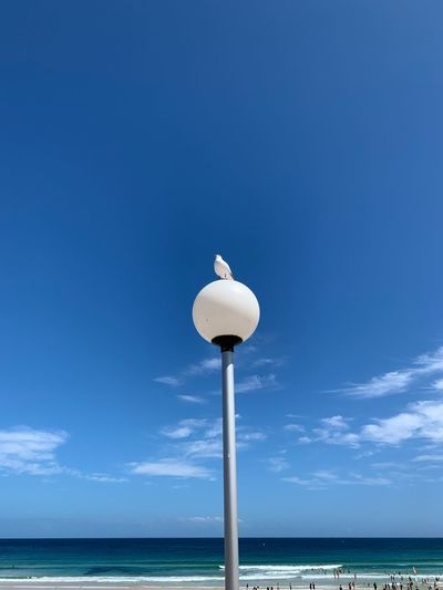 Low angle view of street light by sea against sky