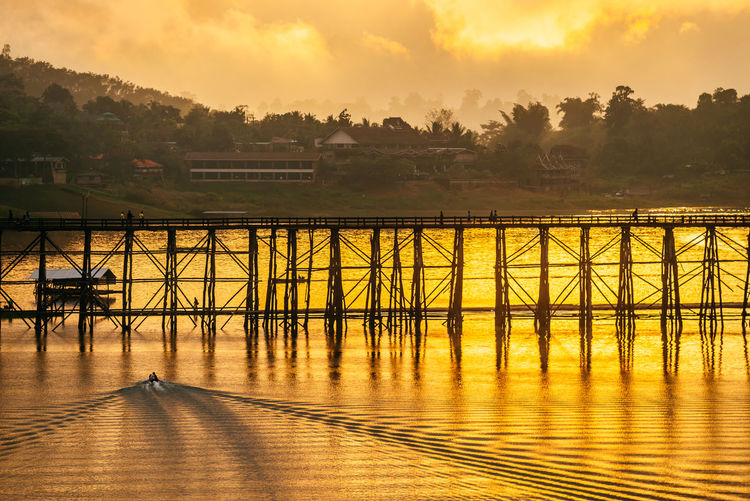 small boat in golden lake Golden Lake Wooden Bridge Boat Lake Twilight Silhouette Golden Sun Water Sunset Reflection
