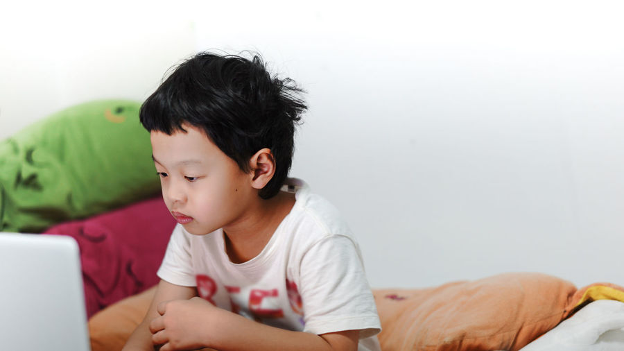 Boy looking away while sitting on bed at home