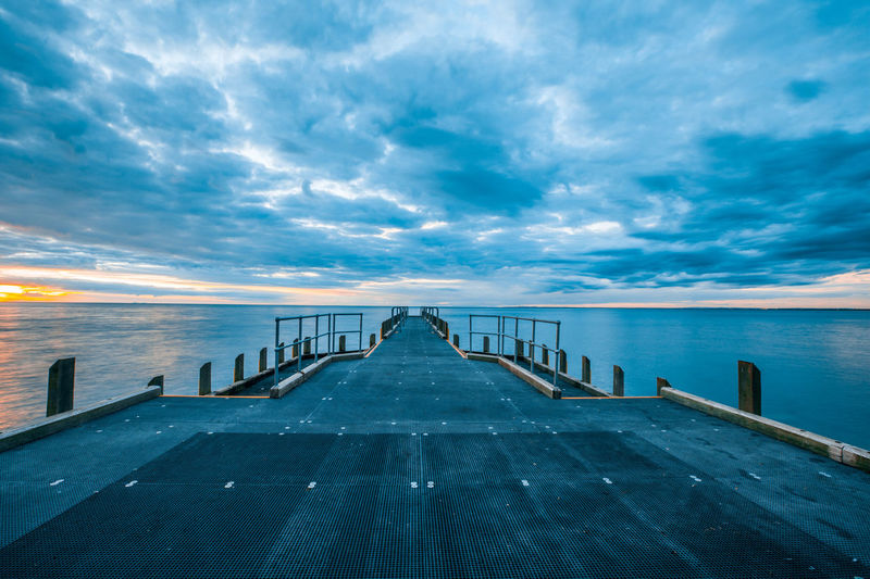 Wooden Jetty In Sea Against Sky