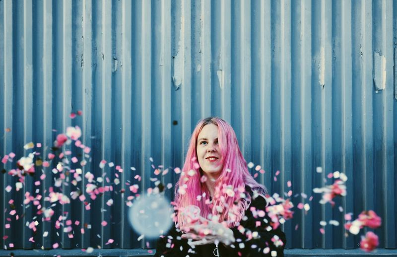 Smiling woman standing by petals in mid-air against corrugated iron