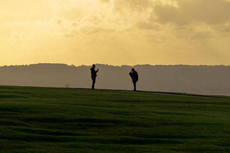 Silhouette man standing on golf course against sky during sunset