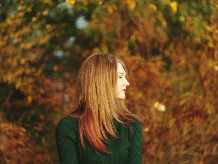 Young woman with eyes closed in park during autumn